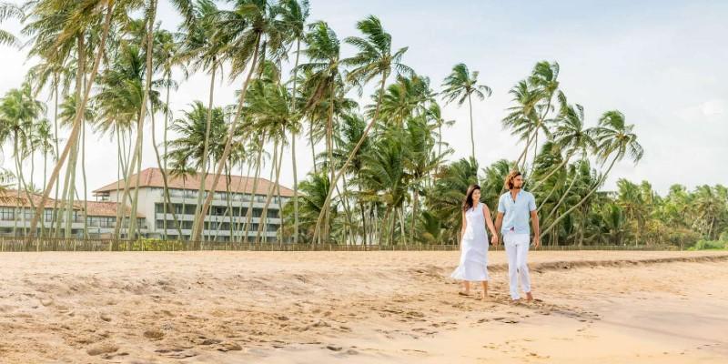 Man and woman walk along the beach at Blue Water Hotel Sri Lanka