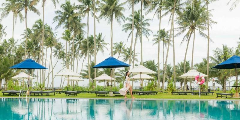 Woman walking along the side of the main pool at Blue Water Hotel Sri Lanka