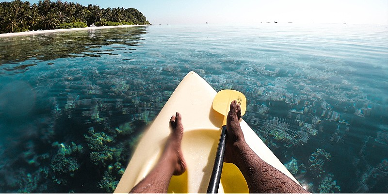 man kayaking over crystal clear waters