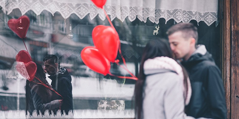 man and a woman kiss on the street with two red heart ballons