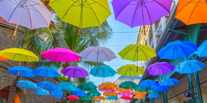 Colourful umbrellas sit on strings above the shoppers on Le Caudan Waterfront