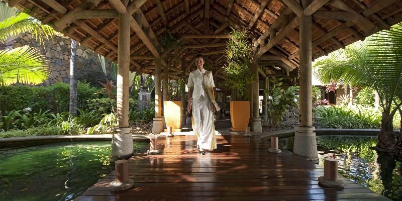A woman walks through along the entrance path at Heritage Awali Golf & Spa Resort