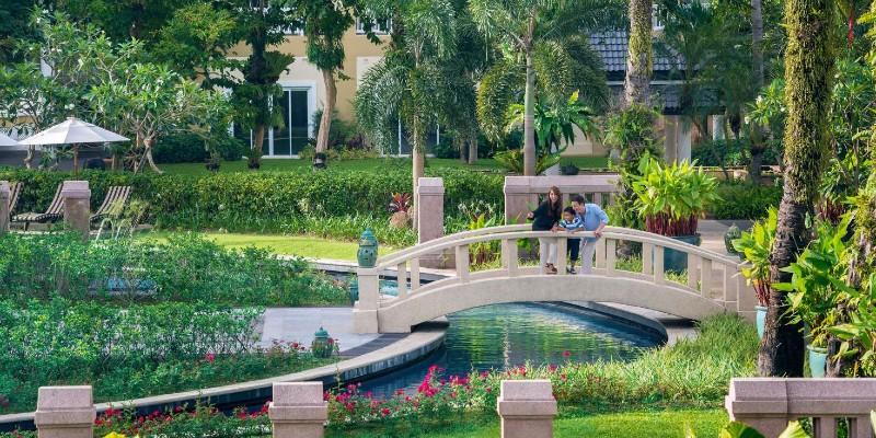 Woman and child walk across a bridge in a Thailand resort garden