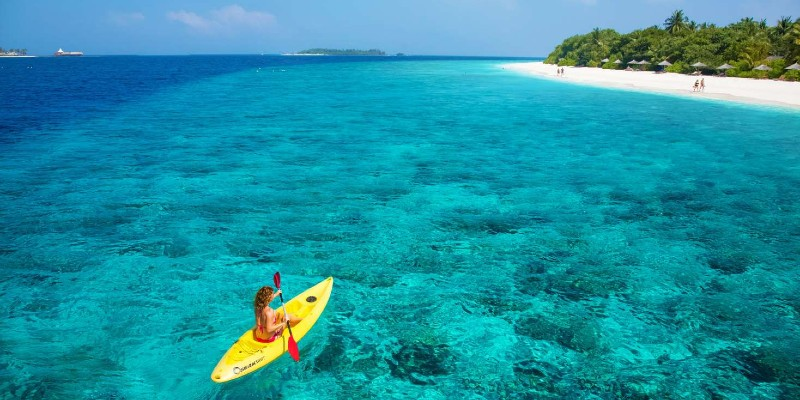 A woman kayaking in the azure waters of the Indian Ocean