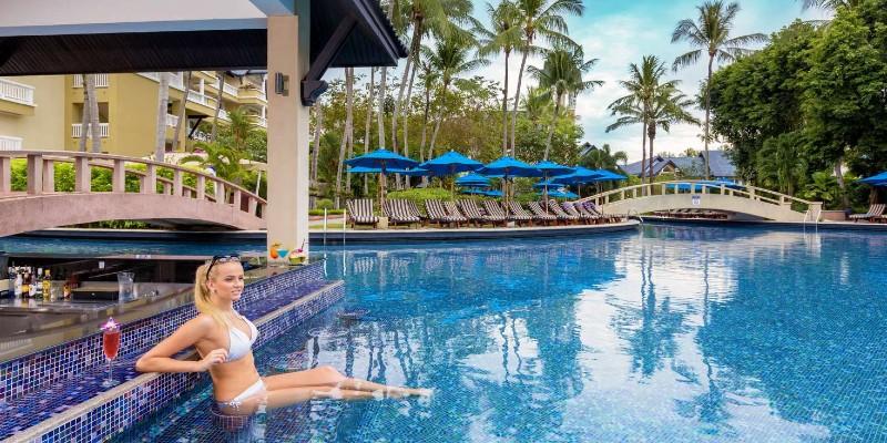 Woman relaxing at the swim-up bar at Angsana Thailand resort
