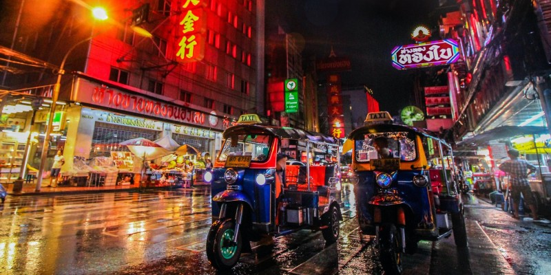 Two tuk-tuks wait on the street at night in Bangkok under the light of colourful neon signs