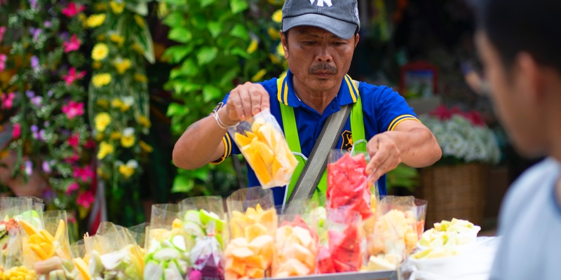 Man arranging gifts on a market stall in Bangkok