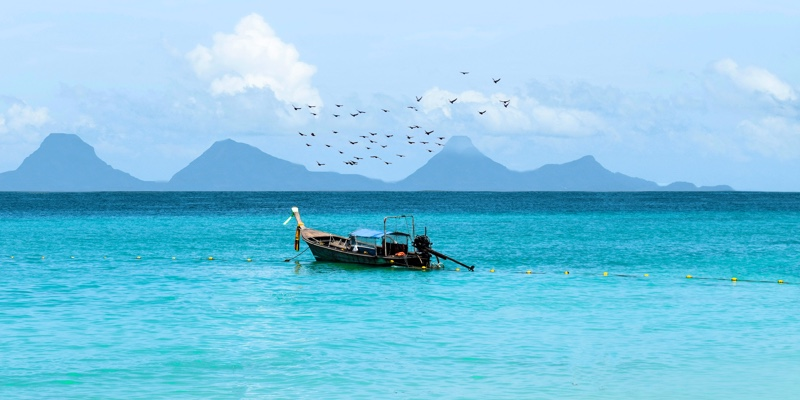 A boat with birds flying above it in the waters of Phang Nga Bay, Thailand