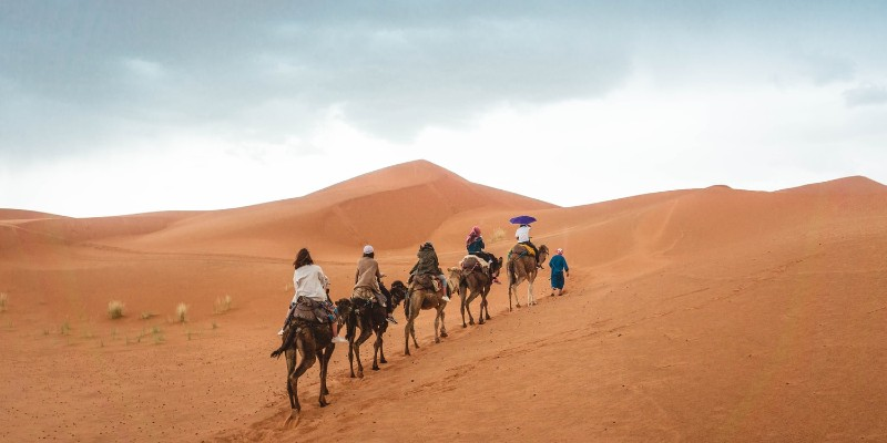 Five people ride camels through the desert in Dubai