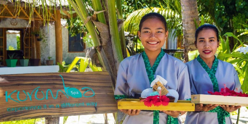 A smiling woman welcoming you to Kurumba spa