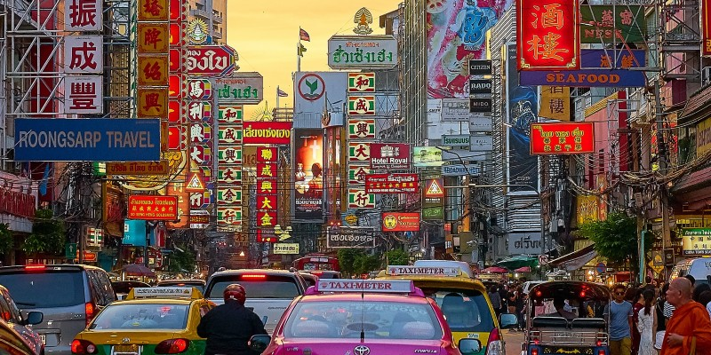 Taxi's, people and colourful signs on the streets of Bangkok