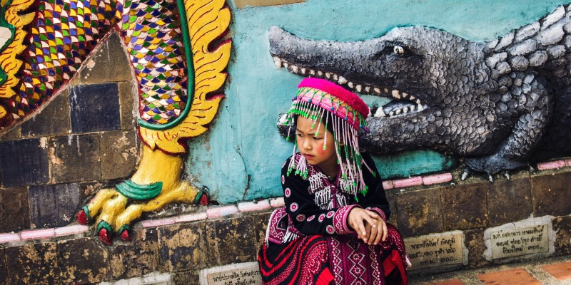 Thai girl sits in front of a wall mural