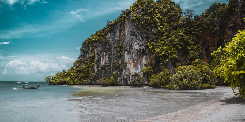 A beach in Thailand surrounded by limestone cliffs