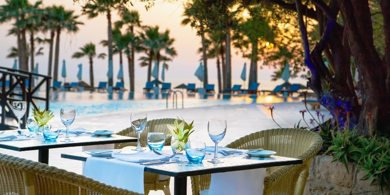 Tables laid for dinner with the pool in the background