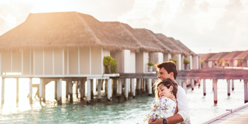 A couple by water villas in the Maldives
