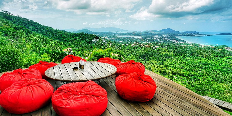 Table and bean bag chairs lookout out over the Thai jungle